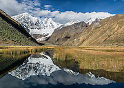 At Incahuain campground, Rio Jahuacocha reflects Mount Jirishanca (Icy Beak of the Hummingbird, 6126 m or 20,098 feet). Day 8 of 9 days trekking around the Cordillera Huayhuash in the Andes Mountains, one day's walk from LLamac, Peru, South America. This panorama was stitched from 3 overlapping photos.