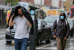 © Licensed to London News Pictures. 05/05/2021. London, UK. A man is caught in heavy rainfall in north London. More rain and sleet is forecasted for the South East this week. Photo credit: Dinendra Haria/LNP