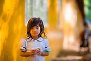 A girl holding a plastic cup of water outside a schoolroom, SALT Ministeries Orphanage Home and School, Siem Reap, Cambodia