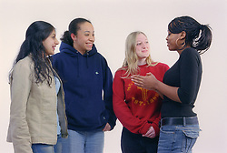 Multiracial group of teenage girls standing together talking and smiling,