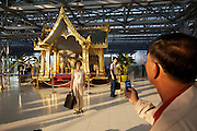 Bangkok's brand new Suvarnabhumi airport. Tourists taking souvenir photos with a throne used by his majesty the King during the airport inauguration ceremony.