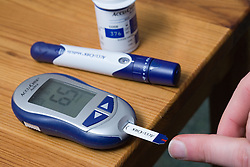 Man using a Accucheck monitor for Diabetes,
