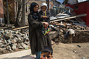 A displaced villager stands amidst collapsed homes in Abikarpora village on the Dal Lake, Srinagar, Jammu and Kashmir, India, on 25th March 2015. Nearly 2500 villagers including Srinagar, the capital of the state of Jammu and Kashmir, was devastated by severe floods and landslides in September 2014 the worst in 60 years, displacing millions of people, many of them children. Photo by Suzanne Lee for Save the Children