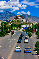 Traffic on a road with the Potala Palace (a UNESCO World Heritage Site) in background. The palace was the chief residence of the Dalai Lama until the 14th Dalai Lama fled to Dharamsala, India, during the 1959 Tibetan uprising. The massive palace contains 999 rooms. Lhasa, Tibet, China.