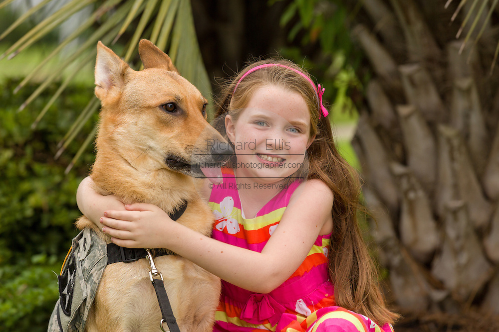 Rachel Mennet, a third-grader, poses with service dog Abel on September 23, 2014 in Summerville, South Carolina. Rachel led a successful fundraising effort using her lemonade stand to pay for training Abel to become a service dog for wounded warrior Nick Bailley.