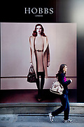 Woman walks past an advertising poster for Hobbs fashion store. London.