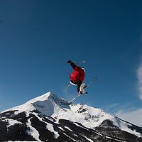 Young skiers and snowboards ride over jumps and in a half pipe in a terrain park at Big Sky Resort, Montana