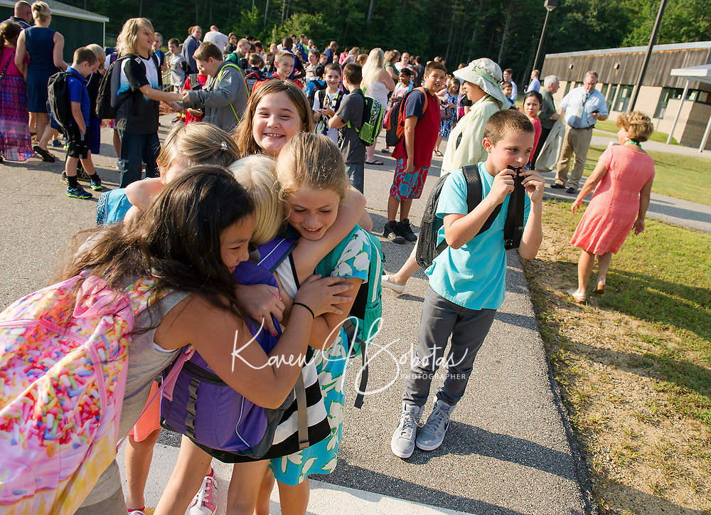 Peyton Mills (in center) gets a group hug from Keirah Sanborn, Zaria Ainsworth, Phoebe Townsend and Mia Lynch as they begin their first day of 5th grade on Monday morning at Woodland Height Elementary School.  (Karen Bobotas/for the Laconia Daily Sun)