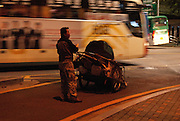 A homeless Korean man waiting for an oppotunity to cross a busy intersection with his handcart