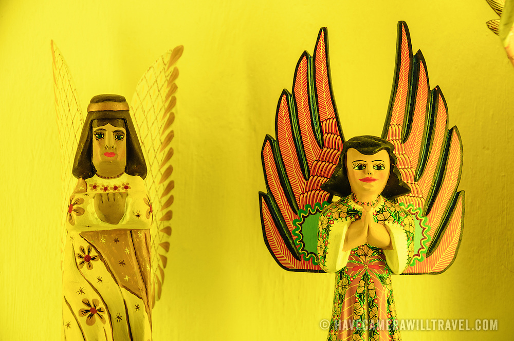 Wooden angel figurines against a bright yellow wall at Xcarat Maya theme park south of Cancun and Playa del Carmen on Mexico's Yucatana Peninsula.