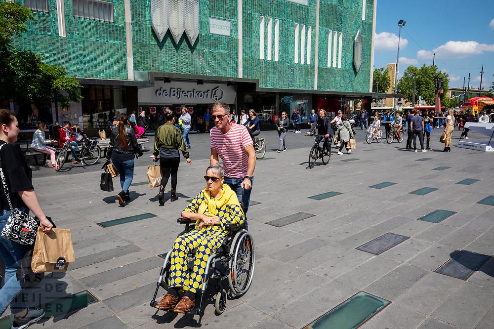 In Eindhoven duwt een man een vrouw in een rolstoel voort voor de Bijenkorf aan het 18 septemberplein.<br /> <br /> In Eindhoven a man pushes a woman in a wheelchair.