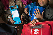 (Alison Griffin to fill in names) (Name) holds the solar lamp as her children hold other emergency kit items inside their temporary shelter in Abikarpora village on the Dal Lake, Srinagar, Jammu and Kashmir, India, as seen here on 25th March 2015. Since the flood, she has been widowed, and is left with four young children and no home. Her family now lives in a temporary shelter built using the emergency shelter kit, and continues their recovery with the help of relief kits such as education kit, food basket, hygiene kit and non-food items from Save the Children. Photo by Suzanne Lee for Save the Children