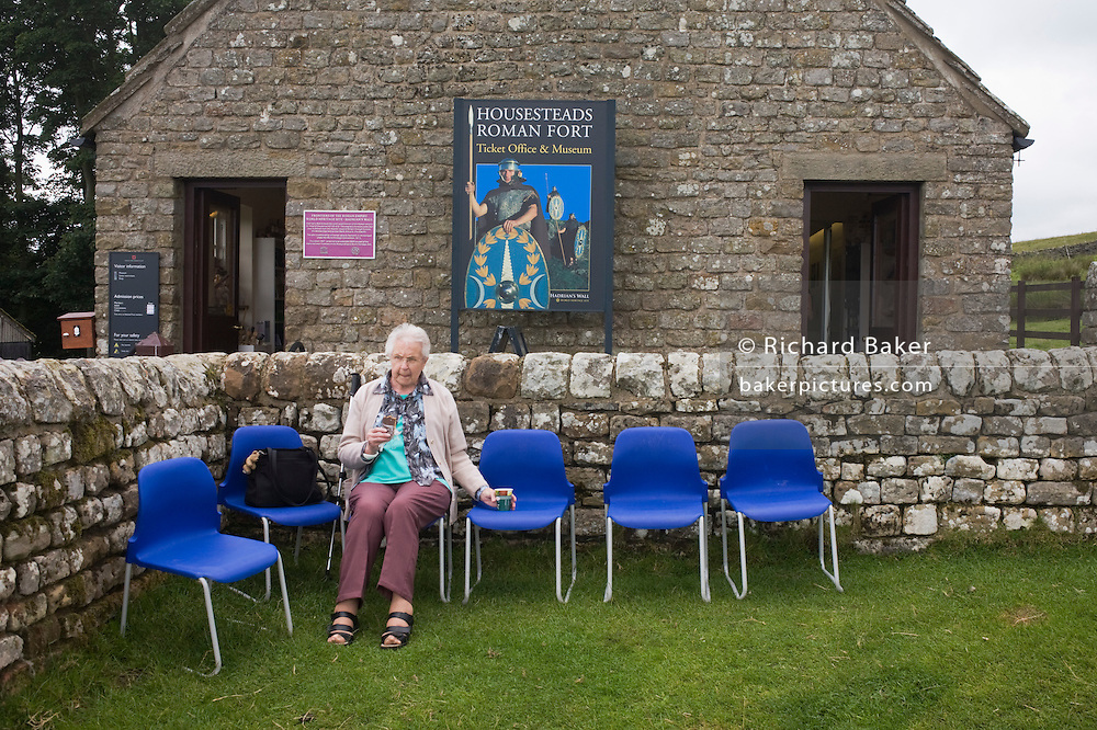 Elderly visitor rests at Housesteads Fort on Roman Hadrian's Wall, once the northern frontier of Rome's empire.