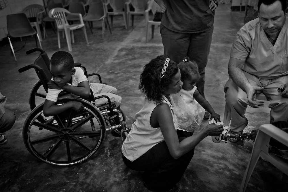 Jay Tew of the Hanger Clinic inspect and make necessary adjustment to the prosthetic leg of 4 yrs. old Tijoelle.  Due to their growth spurt, children needs to come in once a month minimum but definitely every 3 months and needs to be changed once a year.<br /> <br /> Hanger Clinic in Deschapelles, 120km from Port Au Prince, had provided artificial limbs to more than 500 earthquake victims.  The clinic also employs Haitians with few foreign specialists who volunteers two weeks at a time.  On average, the clinic helps 40 patients per day with prosthetics, physical therapy, adjustment and repairs, and counseling for free. Their funding and support comes from Hanger Orthopedic Group, Hanger Ivan R Sabel Foundation, Hospital Albert Schweitzer (HAS) and private donations.  Many patients travel hundreds of miles to the clinic to get treatment.  The clinic arranges transportations and offers lodging for patients needing to stay longer.