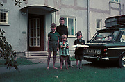 Children in Germany stand in front of a house next to a British Army-registered Singer Chamois aka Hillman Imp car, on 13th July 1970, in Lippstadt, Germany.