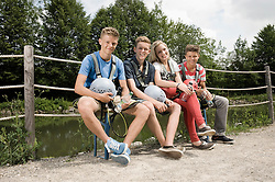 Portrait of teenage boys and teenage girl relaxing on bench, smiling