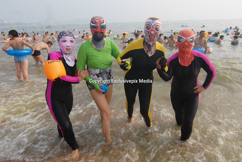 QINGDAO, CHINA - AUGUST 02: (CHINA OUT) <br /> <br /> Four women swimmers wearing face-kinis with Beijing Opera types pose in Qingdao\'s First Bathing Beach on August 2, 2015 in Qingdao, Shandong Province of China. The locally designed face-kinis to protect against sunshine. The first generation of face-kini was invented by lady Zhang Shifan and now the new forth generation of face-kinis with Beijing Opera types and the fifth generation of face-kinis that are one-pieces gain popularity among swimmers. <br /> ©Exclusivepix Media
