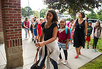 Mrs. Besegai follows her 5th grade students into Elm Street School Thursday morning to begin their first day of classes.  (Karen Bobotas/for the Laconia Daily Sun)