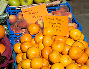 Close up of Spanish peaches and oranges for sale, England, UK