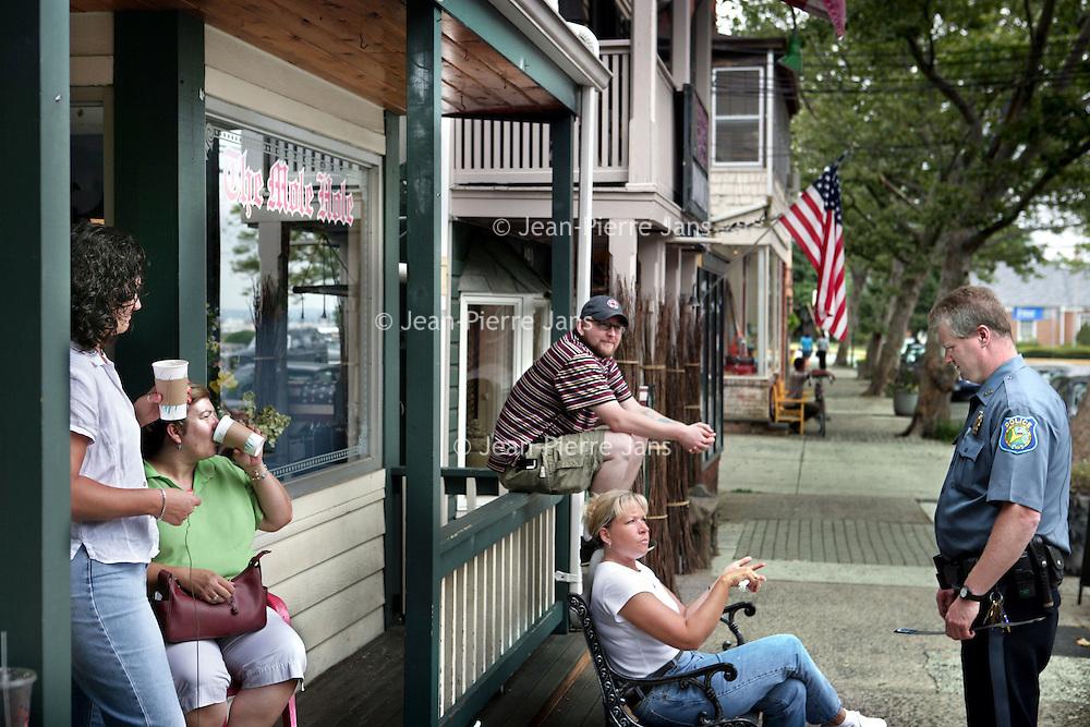 Verenigde Staten.Piermont.New York State.Rockland. 8 juli 2005.<br /> Straatbeeld in het centrum van Piermont, een dorpje aan de rivier de Hudson zo'n 30 km buiten New York city.<br /> Op de foto: agent maakt praatje met buurtbewoners.Politieagent.autoriteit.Terras.Ontspannen.Layd backAmerikaanse vlag.Trots.Nationaal gevoel.Public service<br /> Archives 2005, in the streets of Piermont, New York USA.