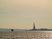 Silhouette of the Statue of Liberty seen from a distance.