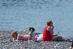 © Licensed to London News Pictures. 29/05/2016. Aberystwyth, Wales, UK. On a fine sunny and very warm Sunday afternoon, people enjoy the sunshine on the beach and on the promenade in Aberystwyth on the coast of Cardigan Bay, west Wales. The temperature is set to reach 22ºc by the mid-afternoon, and the fine weather is forecast to continue into the Bank Holiday Monday in the west, though with the threat of rain in the south east of the UK .  Photo credit: Keith Morris/LNP