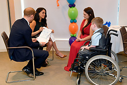 The Duke and Duchess of Sussex look at a t-shirt designed by William Magee and mother Kelly during the annual WellChild Awards at the Royal Lancaster Hotel, London.