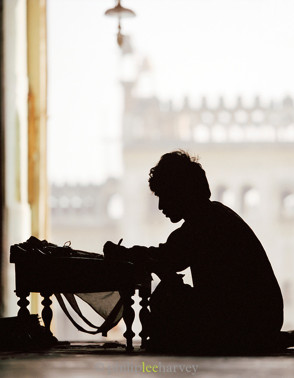 Scribe working at a traditional Indian writing desk, Lucknow, Uttar Pradesh, India