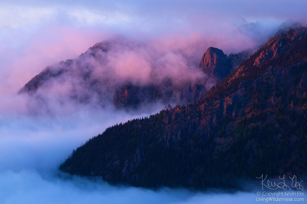 Mount Angeles is obscured by thick clouds and fog. This sunset scene was captured from the summit of a rocky peak along the Hurricane Hill trail in Olympic National Park, Washington.