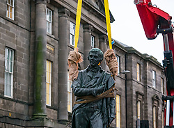 Leith, Edinburgh, Scotland, United Kingdom, 11 December 2019, Trams to Newhaven: The well-known statue of Robert Burns by David Watson Stevenson unveiled in 1898 in Bernard Street is removed by crane to make way for the Trams to Newhaven construction work. It will be restored and stored until it can be replaced at a nearby location once the work is complete.<br /> Sally Anderson / EdinburghElitemedia