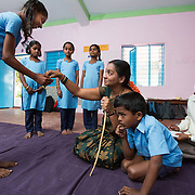 CAPTION: While Cluster Resource Person (CRP) Basavaraju observes, Sunithamma leads her primary school class in enacting a skit called 'Grandmother's Pride'. This group work exercise taught by The Teacher Foundation (TTF) is especially useful for including children with special needs. Roopa (left), for example, loves acting. She has a learning disability and used to come to class only very irregularly. Now that these activities are included in the lesson plan, she's happy to come much more often. LOCATION: Mariallahundi (village), Kasaba (hobli), Chamrajnagar (district), Karnataka (state), India. INDIVIDUAL(S) PHOTOGRAPHED: From left to right: Roopa S., Kavya P., Kavya M.P., Mamatha M., Sunithamma, Sunil M.K. and Basavaraju M.