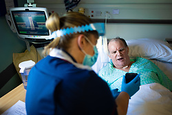 © Licensed to London News Pictures . 11/02/2021. Wythenshawe , UK . A member of ward staff holds a phone for patient KEVIN CRAMPTON (59) , as he takes a video call from his sister . Kevin had been ventilated and proned on the route to recovery from Coronavirus . Covid positive patients are treated for the effects of Coronavirus in Wythenshawe's A1 Respiratory Ward . Photo credit : Joel Goodman/LNP