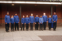 Multiracial group of secondary school pupils standing in row wearing uniform,