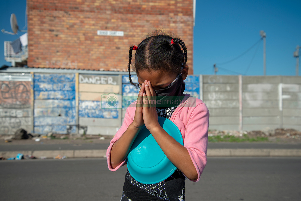 """A young girl hugs her empty plate as she prays, in Parkwood, Cape Town, South Africa, on Sunday, May 31, 2020. The joint prayer in Afrikaans opened a special chicken lunch served by the Parkwood Community Upliftment (PCU) project. The youth organization, which normally feeds children as part of an after-school care program, has been feeding children, the elderly, and many other hungry people, in this poverty-stricken area in the Cape Flats since lockdown started more than two months ago. As the nation moves down to Level 3, on June 1st, CPU founder Max Amansure says the organization will continue to feed people. Often it's """"only"""" bread as the organization doesn't have any regular funding. However, as the area has been hard hit by COVID-19, Amansure says he wishes Parkwood could have remained on Level 5 Lockdown. PHOTO: EVA-LOTTA JANSSON"""