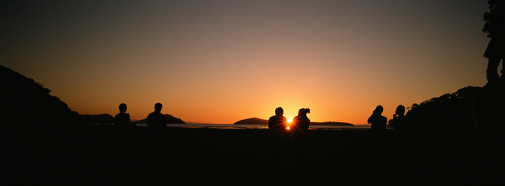 Tourists watch the sunset over the bay area of Shelly Beach, on the Coromandel Peninsular adjourning the Shelly Beach TOP 10 Holiday Park, a popular tourist destination. Coromandel Peninsular, North Island, New Zealand. Photo Tim Clayton