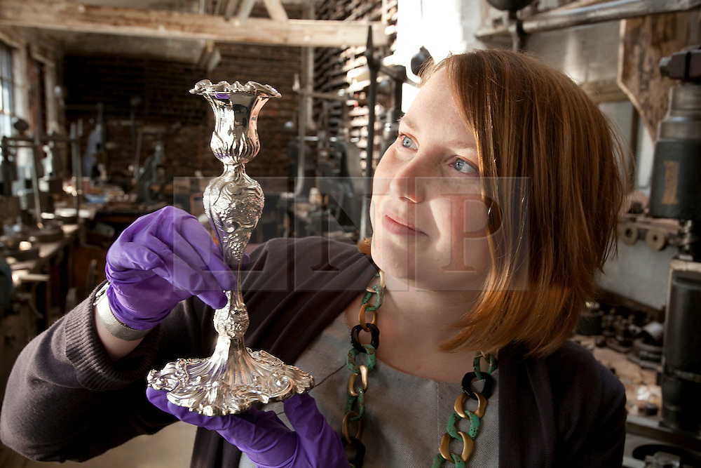 © licensed to London News Pictures. 19/05/2011. Birmingham, UK. English Heritage has stepped in and aquired JW Evans silver workshop to save it, and its contents, from developers. A family Silverware factory founded in 1881 in the heart of Birmingham's historic jewellery Quarter. Pictured, Holly Woodward from English Heritage holding a candlestick produced at the factory. Please see special instructions for usage rates. Photo credit should read Dave Warren/LNP