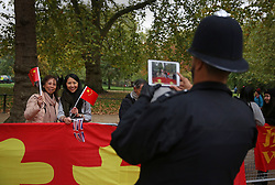 © Licensed to London News Pictures. 20/10/2015. London, UK. A policeman takes a phone photograph of Chinese supporters in The Mall ahead of President Xi Jinping's four day State Visit to the United Kingdom. Photo credit: Peter Macdiarmid/LNP