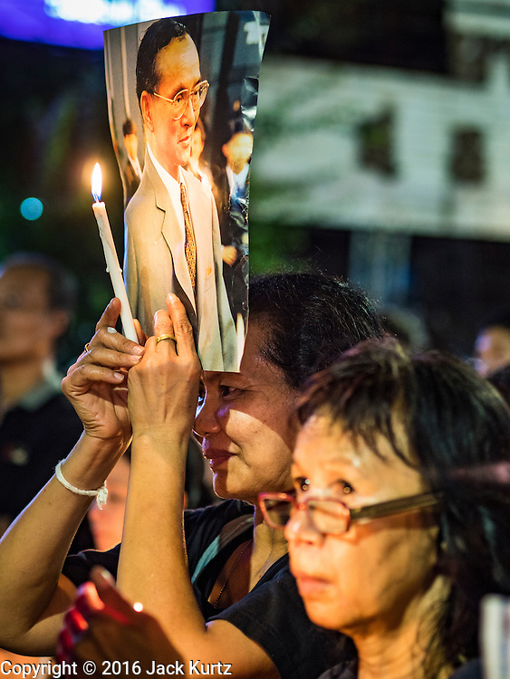 26 NOVEMBER 2016 - BANGKOK, THAILAND: People hold up portraits of the late of Thailand during a candlelight vigil in honor of the revered monarch in Bangkok's Chinatown. Thousands of people gathered on Yaowarat Road in the heart of Bangkok's Chinatown to honor Bhumibol Adulyadej, the Late King of Thailand. The event was organized by the Thai-Chinese community and included a performance by the Royal Thai Navy orchestra of music composed by the Late King, a prayer by hundreds of Buddhist monks. It concluded with a candlelight vigil. The King died after a long hospitalization on October 13. The government has declared a one year mourning period. HRH Crown Prince Maha Vajiralongkorn, the Heir Apparent and Late King's son, is expected to be name the King next week. He will be known as Rama X.       PHOTO BY JACK KURTZ