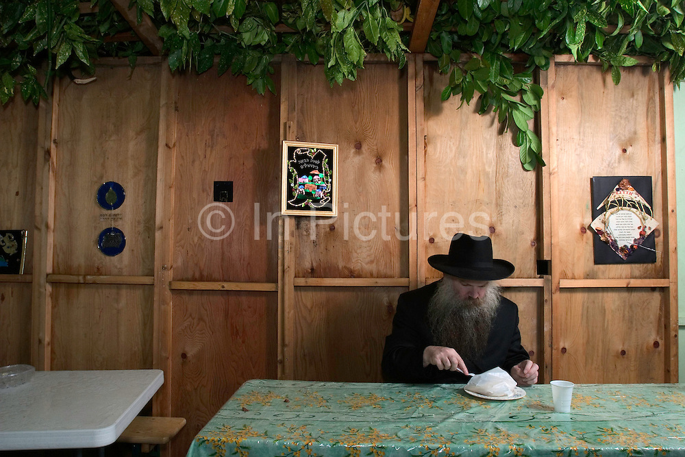 Rabbi Herschel Gluck eating a takeaway meal in his Sukkah during the festival of Sukkot, the feast of Tabernacles. The holiday commemorates the forty-year period during which the children of Israel were wandering in the desert. In honor of the children of Israel in the wilderness, men dwell in temporary shelters. This shelter is called a Sukkah it has at least three sides and a partially open roof covered with greenery.