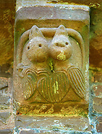 Norman Romanesque exterior corbel no 36 - sculpture of two fledgling birds both biting a serpent. Possibly an allegory of the original sin man is born with due to Adam taking the apple from a serpent in the garden of Eden.  The Norman Romanesque Church of St Mary and St David, Kilpeck Herefordshire, England. Built around 1140 .<br /> <br /> Visit our MEDIEVAL PHOTO COLLECTIONS for more   photos  to download or buy as prints https://funkystock.photoshelter.com/gallery-collection/Medieval-Middle-Ages-Historic-Places-Arcaeological-Sites-Pictures-Images-of/C0000B5ZA54_WD0s