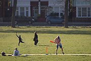 In the third week of the UK governments lockdown during the Coronavirus pandemic, when the daily UK death rate rose by another 761 to 12,868 and with nearly 100,000 reported cases. a London family play cricket during their daily exercises in Ruskin Park, a public green space in the south London borough of Lambeth, on 15th April 2020, in London, England.