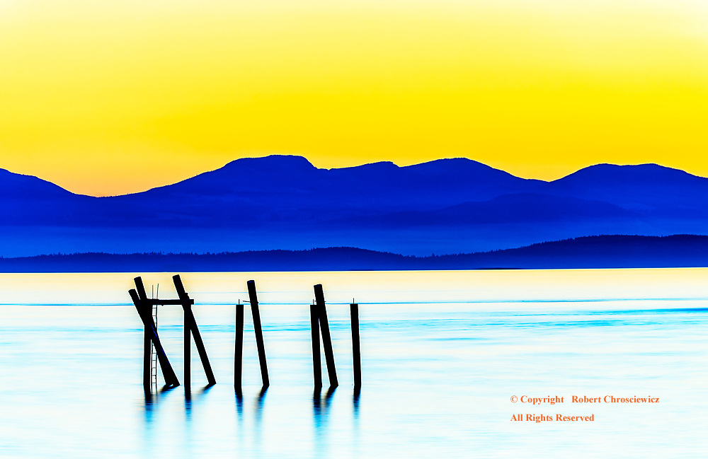Yellow Sky:  Distant Galiano and Vancouver Islands are held in silhouette under a yellow sunset, with the water of the Strait of Georgia captured in this long exposure, Richmond British Columbia Canada.