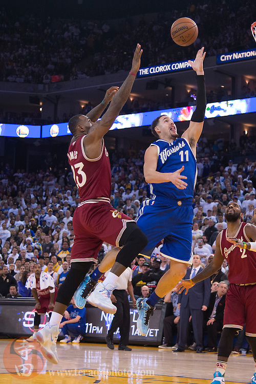 December 25, 2015; Oakland, CA, USA; Golden State Warriors guard Klay Thompson (11, right) shoots the basketball against Cleveland Cavaliers forward LeBron James (23, left) in the fourth quarter of a NBA basketball game on Christmas at Oracle Arena. The Warriors defeated the Cavaliers 89-83.