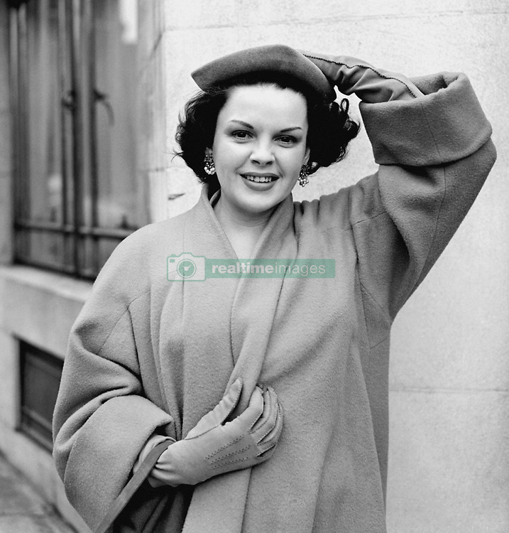 Film actress Judy Garland newly arrived from Hollywood holds her hat against London's playful April breezes as she leaves her Park Lane hotel.