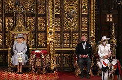 The Prince of Wales and the Duchess of Cornwall seated by Queen Elizabeth II before she delivers a speech from the throne in House of Lords at the Palace of Westminster in London as she outlines the government's legislative programme for the coming session during the State Opening of Parliament. Picture date: Tuesday May 11, 2021.