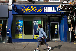 © Licensed to London News Pictures. 09/09/2021. London, UK. A woman walks past a branch of William Hill betting shop in north London. Online gambling group 888 has agreed a £2.2 billion deal to buy William Hill's European business and its 1,400 UK betting shops in a move that will see it return to British hands. Photo credit: Dinendra Haria/LNP