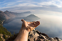 Image of hand holding up Wizard Island.  Crater Lake National Park, Oregon.<br />