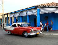 Red car and blue wall in Pinar del Rio, Cuba.