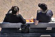 Nederland, Nijmegen, 26-4-2020  Op de Lentse warande zit een stel alvast een biertje te drinken op een bankje langs de spiegelwaal . Konimgsdag 2020 gaat niet door, is afgelast, vanwege de coronadreiging .Foto: Flip Franssen