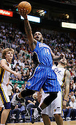 Orlando Magic point guard Jameer Nelson (14) attempts to score as Utah Jazz small forward Andrei Kirilenko of Russia, left, and point guard Deron Williams, right, defend during the first half of an NBA basketball game in Salt Lake City, Friday Dec. 10, 2010. (AP Photo/Colin E Braley)